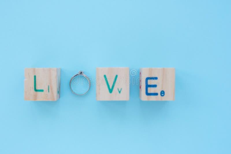 Amore che esprime su un cubo di legno la lettera O sostituisce con un anello fotografia stock