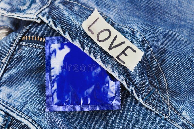 AMORE dell'iscrizione su carta lacerata e sul preservativo in pacchetto blu della stagnola sui jeans fotografie stock