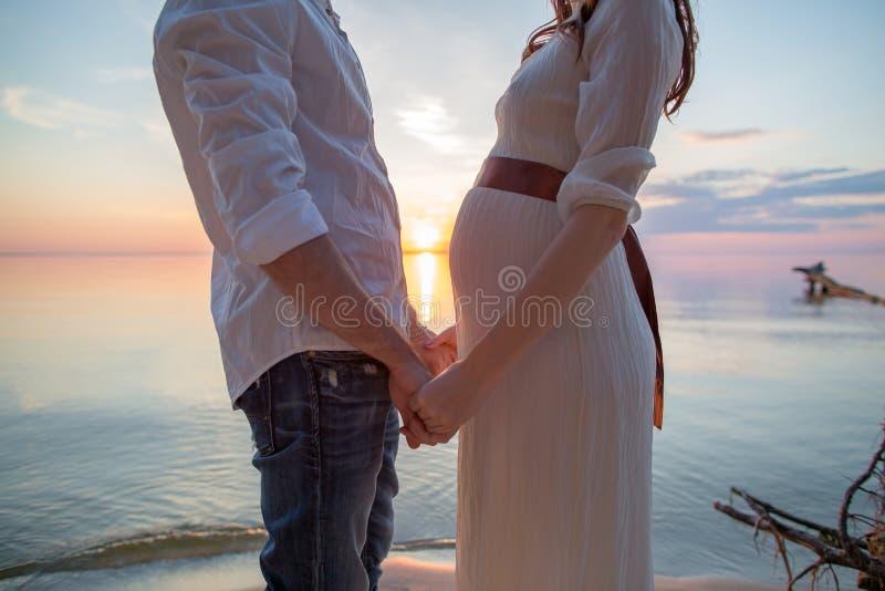 Amore dell'uomo e della donna incinta: due mani al tramonto sulla spiaggia fotografia stock libera da diritti