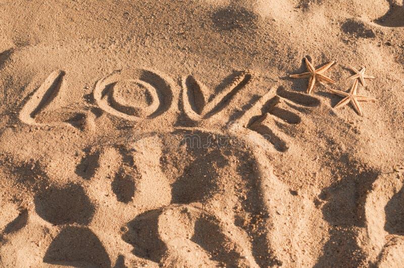 Amore di parola scritto sulla sabbia fotografie stock libere da diritti