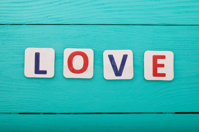 Amore di parola su fondo di legno blu Vista superiore Derisione su Copi lo spazio Giorno di madre del biglietto di S. Valentino immagini stock libere da diritti