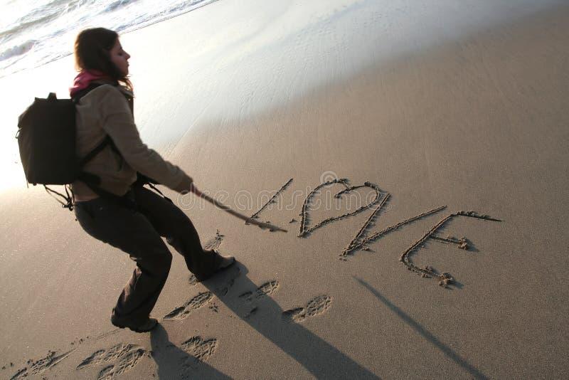 AMORE di scrittura della giovane donna nella sabbia fotografia stock