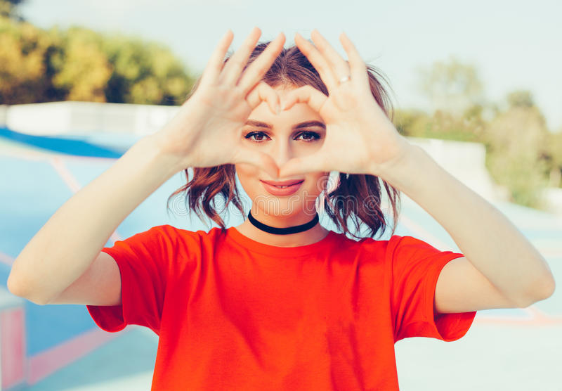 Amore Donna felice sorridente della testarossa del ritratto giovane, facente il segno del cuore, simbolo con le mani Sensibilità  immagine stock