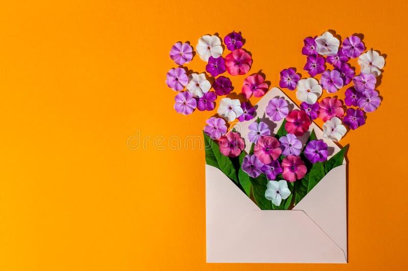Amore - lettera con il fiore, messaggio romantico su fondo di legno arancio Carte di giorno di biglietti di S immagini stock libere da diritti