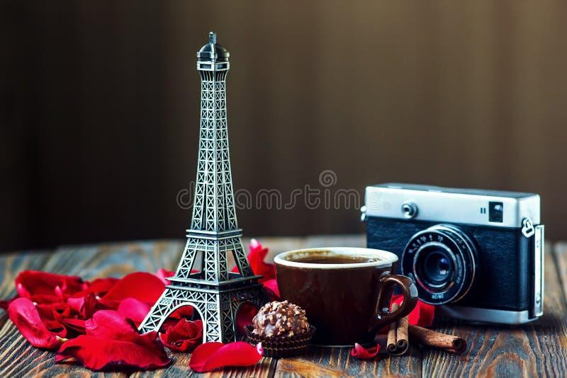 Amore Parigi! Rosa, macchina fotografica d'annata, torre Eiffel, tazza di caffè, cioccolato e bastoni di cannella su fondo di leg fotografie stock