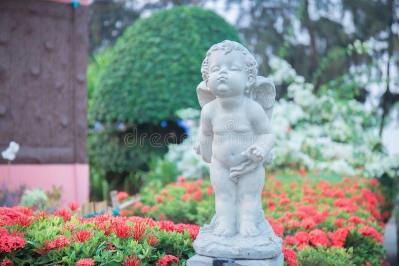 Amorek kamienna statua w kwiatu ogródzie zdjęcie stock