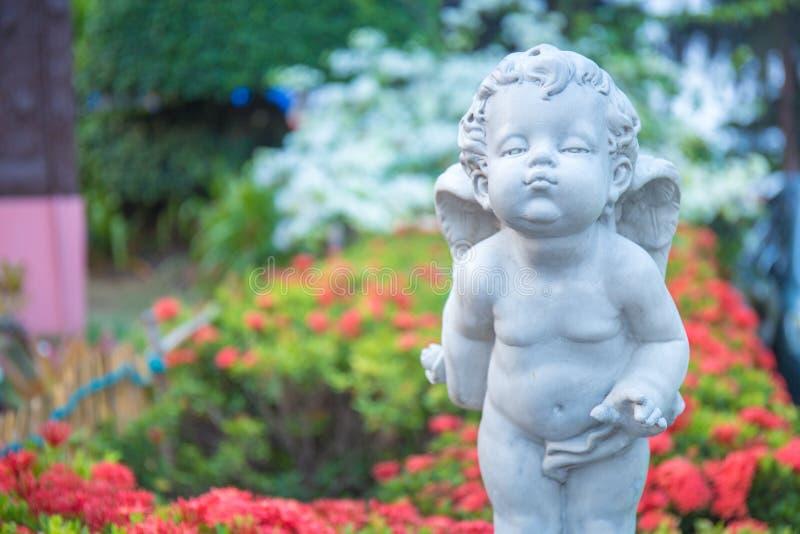 Amorek kamienna statua w kwiatu ogródzie obrazy royalty free