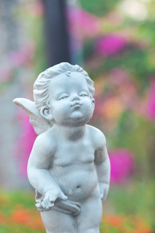 Amorek kamienna statua w kwiatu ogródzie zdjęcia royalty free