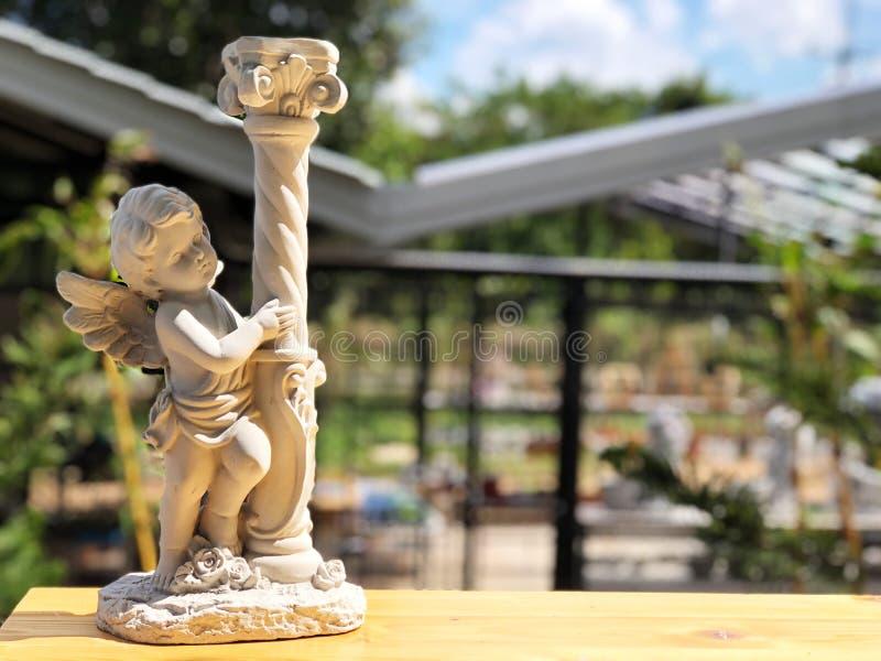 Amorek rzeźby sztuka na drewnianym stole z naturalnym światłem słonecznym zdjęcie royalty free