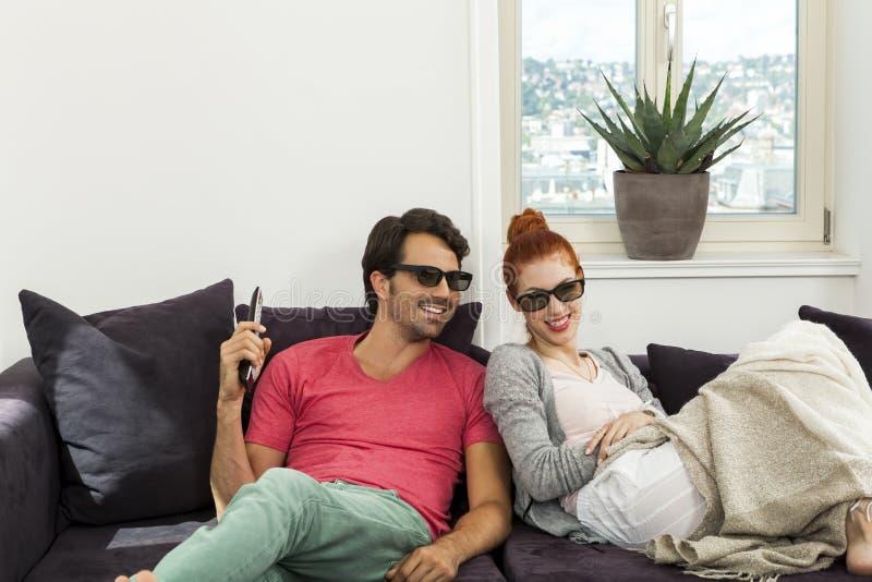 Amores con los vidrios 3d que descansan sobre el sofá imagen de archivo libre de regalías
