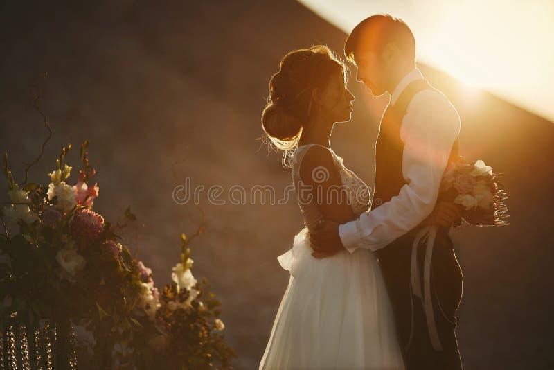 Amores de la silueta en la puesta del sol Muchacha modelo morena hermosa y de moda con el modelado del peinado en el cordón blanc fotos de archivo