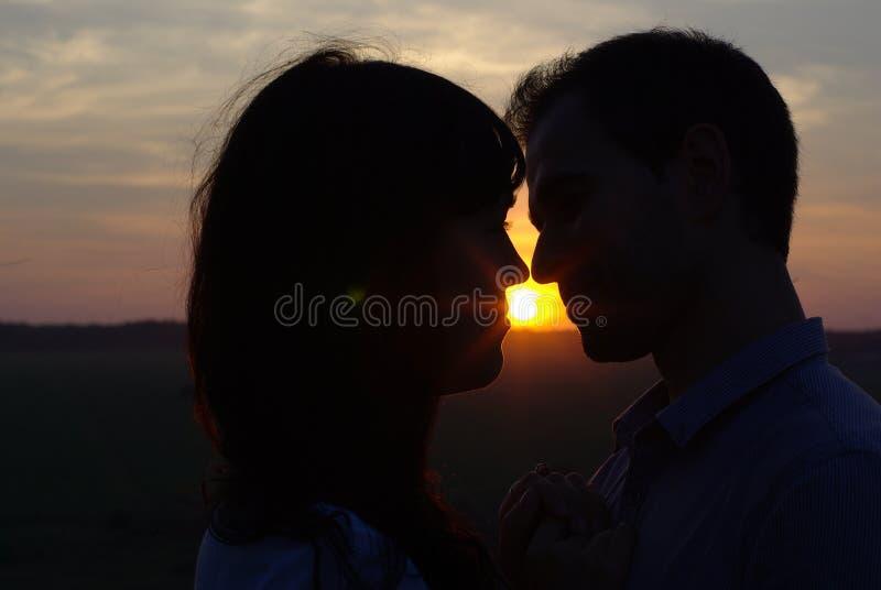Amores de la silueta que se besan en la puesta del sol fotografía de archivo libre de regalías