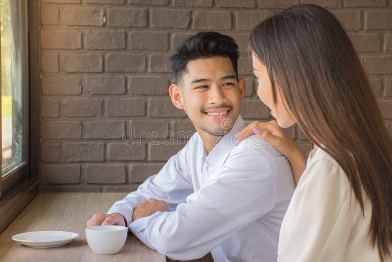 Amores jovenes que sonríen mientras que se sienta en la tabla y el café de consumición en la cafetería/la felicidad y el concepto fotografía de archivo