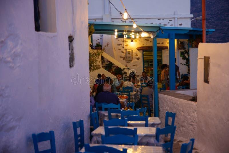 Amorgos, Греция 2-ое августа 2017 Люди есть на традиционном Gre стоковое фото
