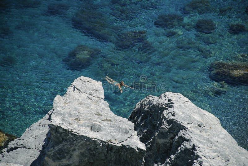 Amorgos, Cyklaöarna, Grekland - den 9 februari 2005: Kvinnors simning i det djupa blåa havet på Mouros strand fotografering för bildbyråer