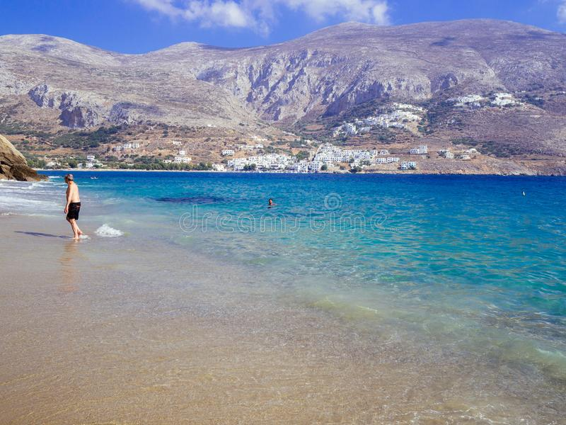 Amorgos, Greece-August 2,2017.The beutiful beach of Psili Ammos, with crystal clear waters and the port of Aegiali in the back. royalty free stock photography