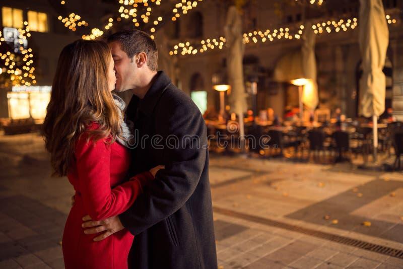 Amorous couple kissing on Christmastime royalty free stock images