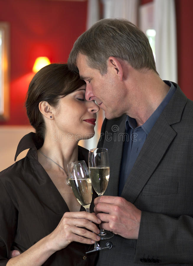 Amorous Couple On Romantic Date. Amorous couple in close embrace standing clinking champagne glasses, showing devotion and trust royalty free stock images