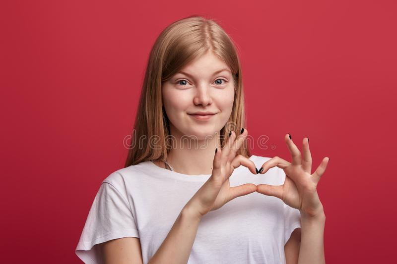 Amorous lovely cheerful girl showing heart gesture with hands. While standing isolated over red background. close up portrait. I love u.You`re in my heart stock photo