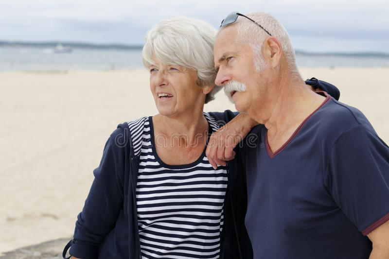 Amorous seniors standing by water against stormy sky. Senior royalty free stock image