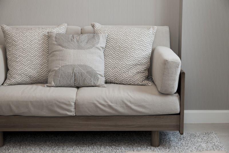 Amortiguador beige en el sofá gris imagen de archivo