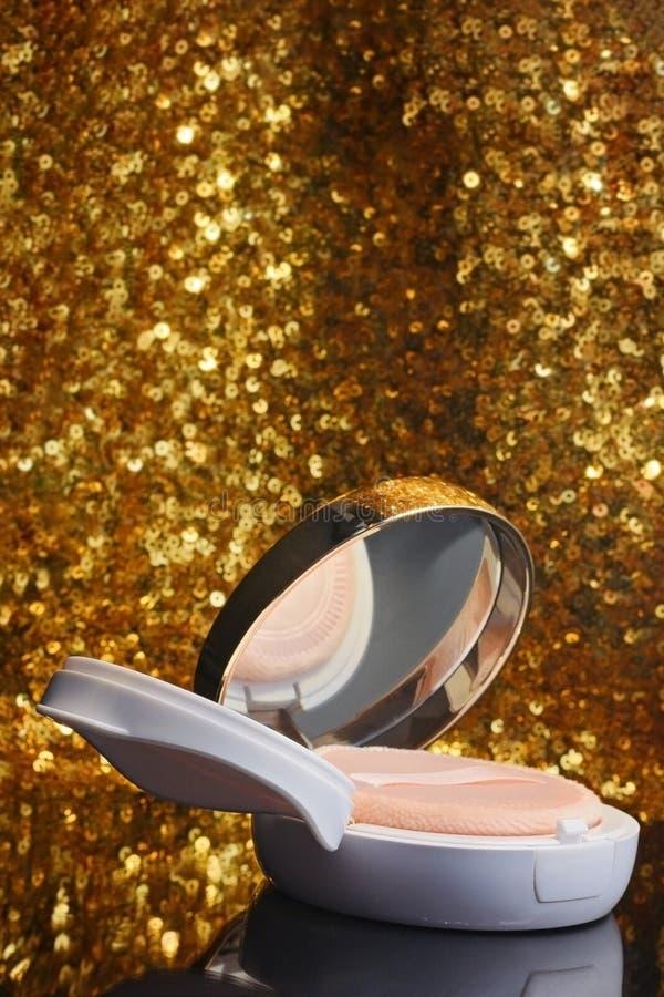 Amortiguador del polvo de la fundación del maquillaje con la reflexión y bokeh de oro que brilla en fondo fotos de archivo