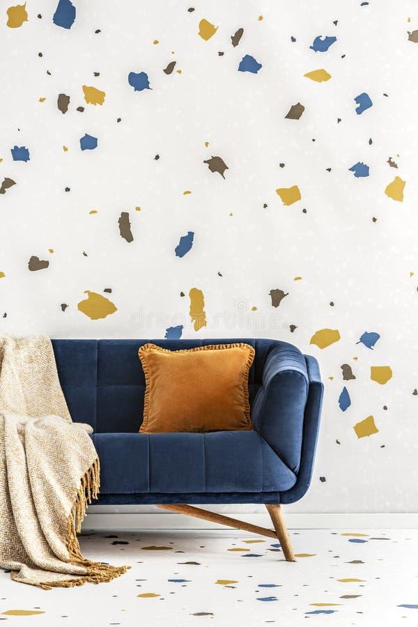 Amortiguador y manta anaranjados en el sofá azul en interior colorido de la sala de estar con el papel pintado Foto verdadera fotos de archivo