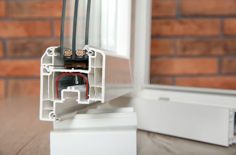 Amostra de perfil moderno da janela no assoalho contra a parede, close up Serviço da instalação fotografia de stock