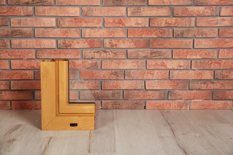 Amostra de perfil moderno da janela no assoalho contra a parede de tijolo, espaço para o texto imagem de stock