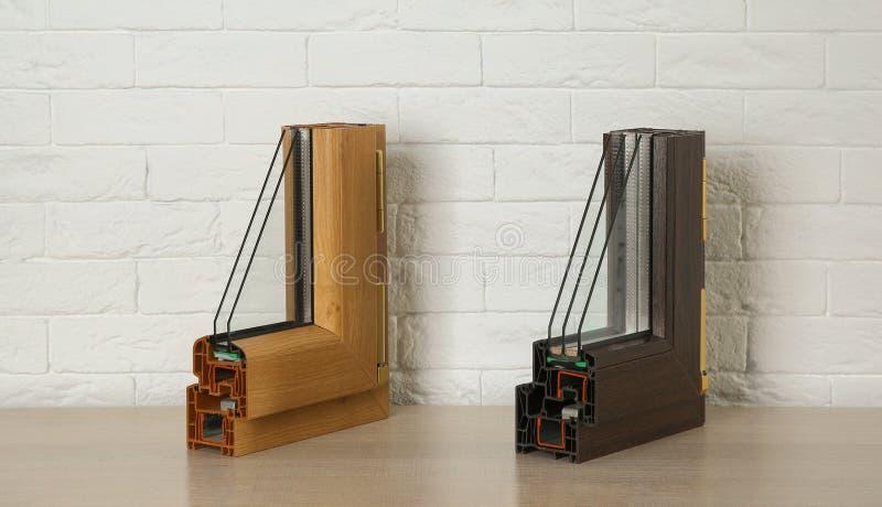 Amostras de perfis modernos da janela na tabela contra a parede de tijolo fotos de stock royalty free