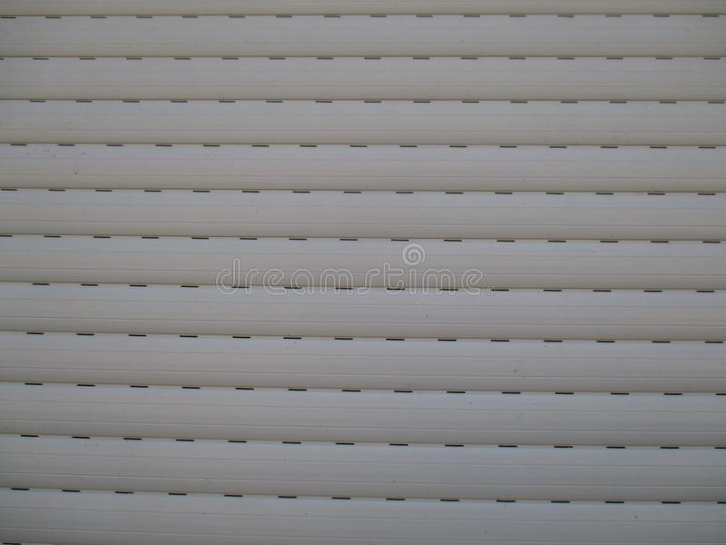 Window shutters with slits for light. The amount of light that is released into the room can be dosed manually or by remote control stock image