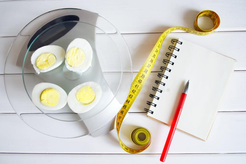 The amount of protein, calories, carbohydrates and fats in food. Cut egg on the kitchen scales. Slim figure, fitness, weight loss, diet and proper nutrition stock images