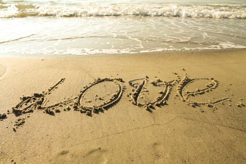 Amour écrit sur le sable photos libres de droits