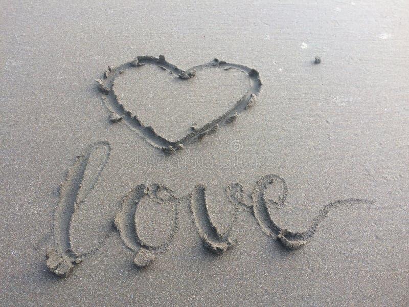 amour écrivant sur le sable de la plage qui a été alors balayée par les ressacs image libre de droits