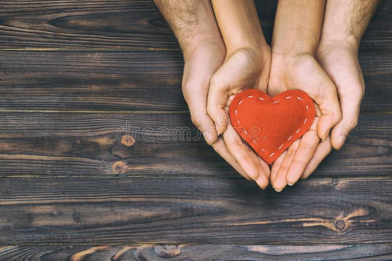 Amour, concept de la famille Fermez-vous des mains de l'homme et de femme jugeant le coeur en caoutchouc rouge ensemble modifié l photo libre de droits