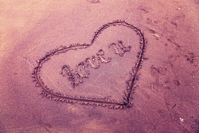 Amour conceptuel de couleur violette de vintage sur le sable de plage image stock