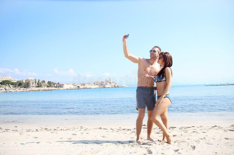 Amour d'été - jeune couple prenant un selfie sur le sable photos libres de droits