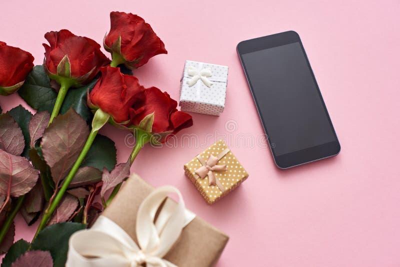 Amour d'application Impressionnez-la avec les roses rouges fraîches, le boîte-cadeau et le téléphone portable noir image stock