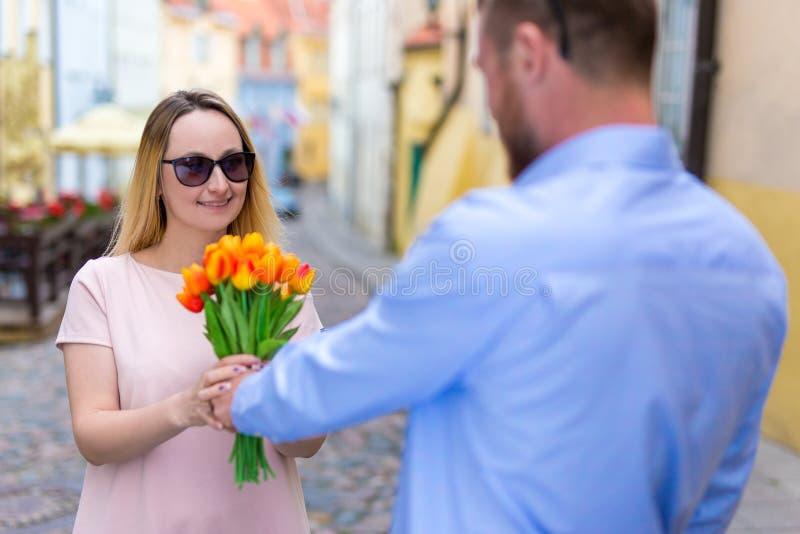 Amour, datation et concept de relations - jeune homme donnant des fleurs photo libre de droits
