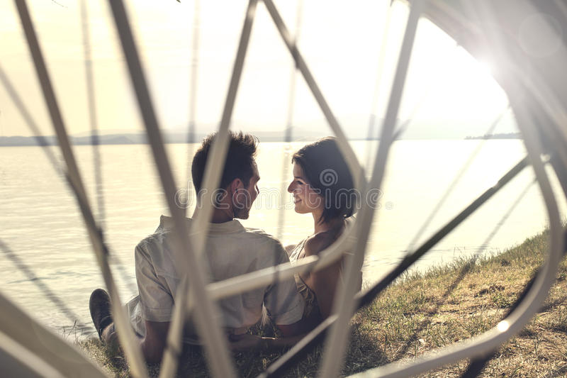 Amour de Couplein avec la bicyclette se reposant devant le lac photo stock