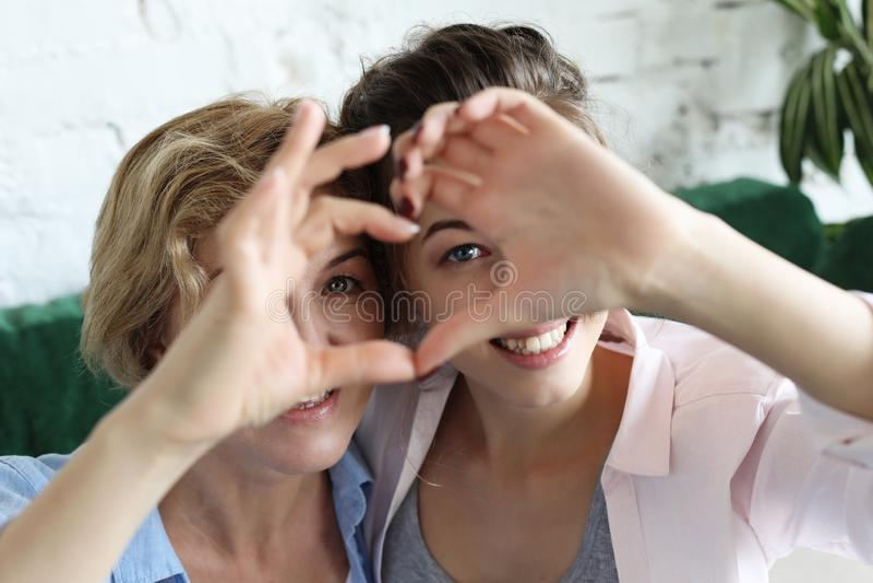 Amour de mère et de descendant Femme adulte et jeune femme empilant des mains dans le signe de coeur regardant l'appareil-photo photographie stock