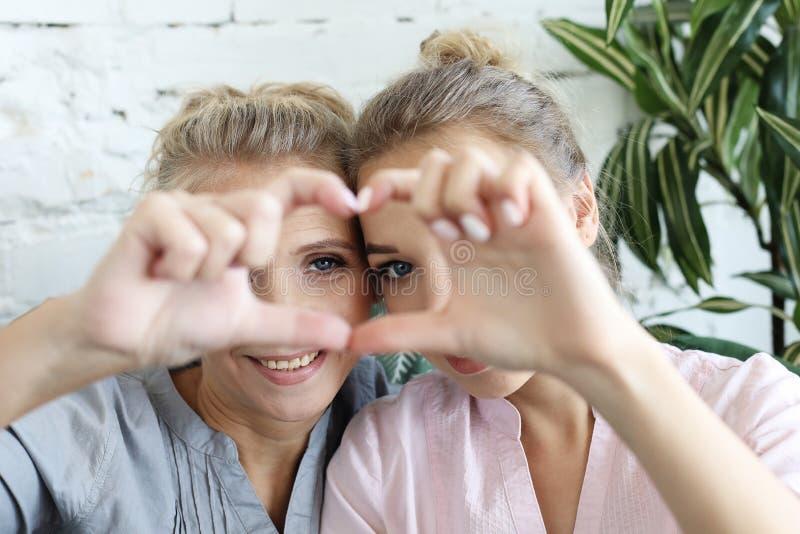 Amour de mère et de descendant Femme adulte et jeune femme empilant des mains dans le signe de coeur regardant l'appareil-photo photographie stock libre de droits
