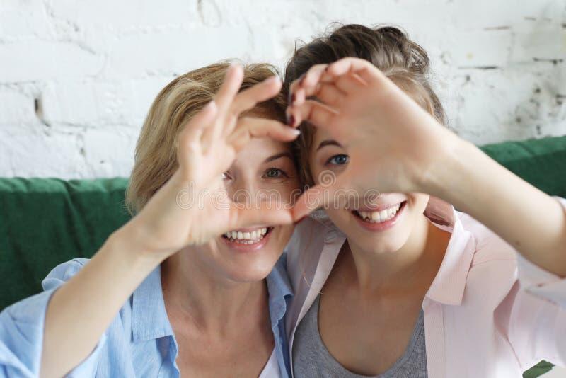 Amour de mère et de descendant Femme adulte et jeune femme empilant des mains dans le signe de coeur regardant l'appareil-photo images stock