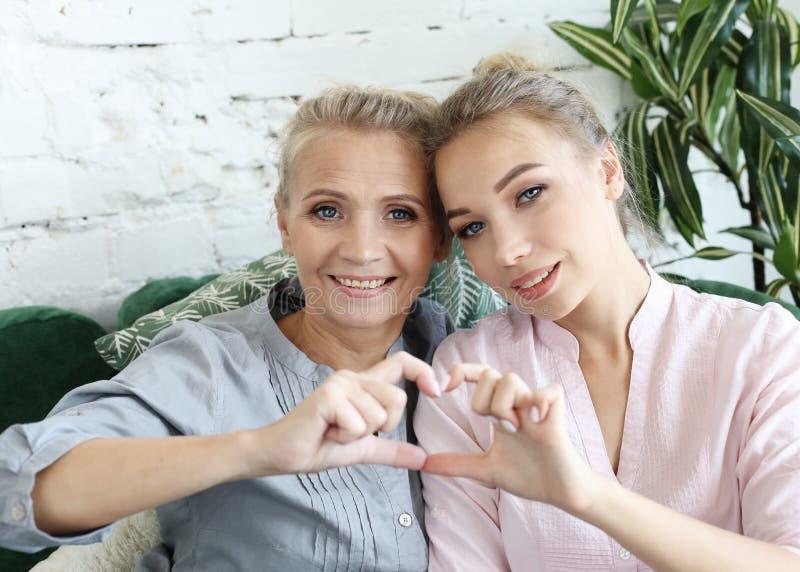 Amour de mère et de descendant Femme adulte et jeune femme empilant des mains dans le signe de coeur regardant l'appareil-photo images libres de droits
