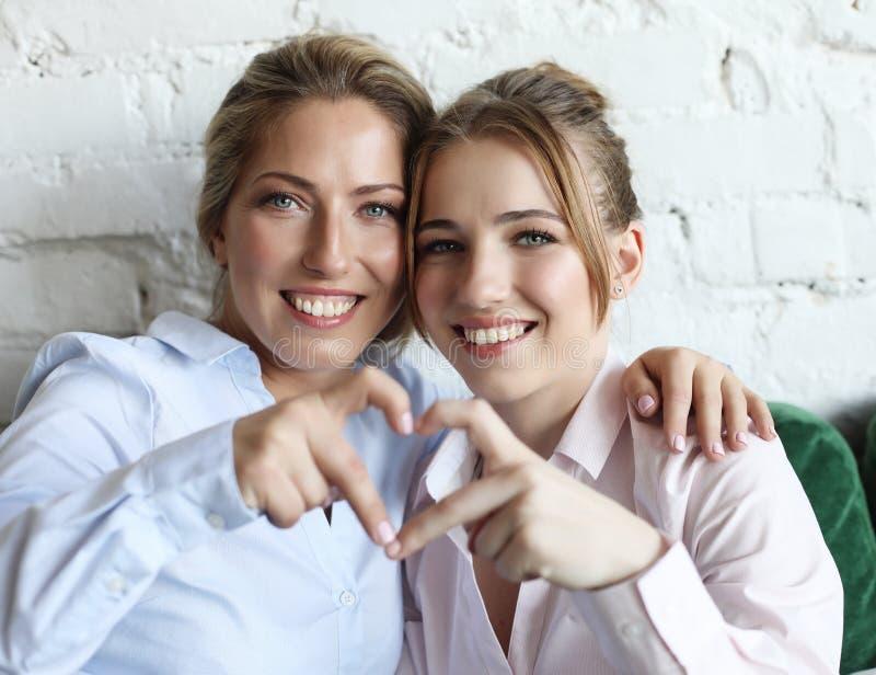 Amour de mère et de descendant Femme adulte et jeune femme empilant des mains dans le signe de coeur regardant l'appareil-photo photos stock