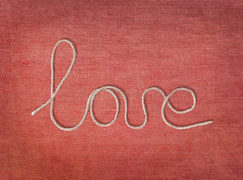 Amour de Word écrit de la corde sur le fond rouge de toile Éléments des textes avec l'ombre sur la texture rose de tissu de coton images stock