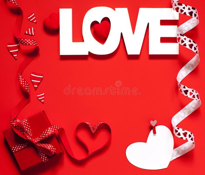 Amour de Word et boîte-cadeau rouge au fond rouge, concept de Valentine Day photographie stock libre de droits