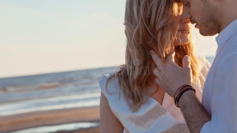 Amour, roman, promenade Portrait bien aéré de beaux couples embrassant sur le fond de la mer de coucher du soleil, de la plage sa photographie stock libre de droits
