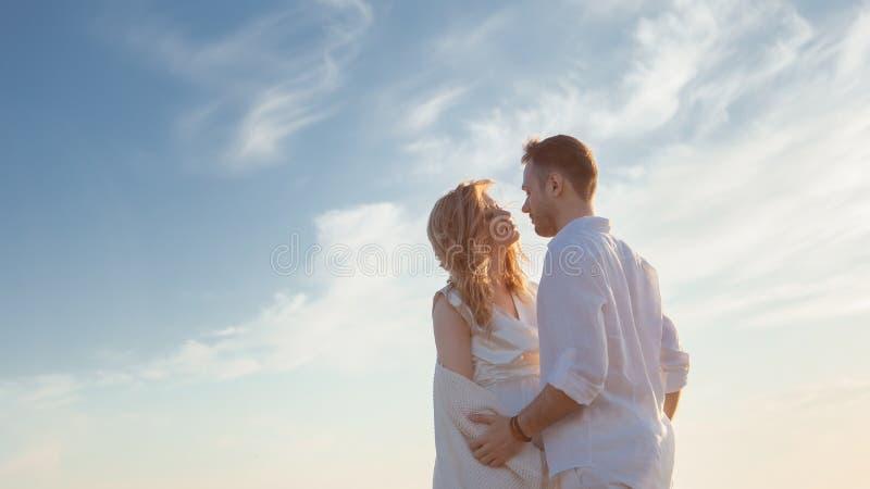 Amour, roman, promenade Portrait bien aéré de beaux couples embrassant sur le fond de la mer de coucher du soleil, de la plage sa image libre de droits