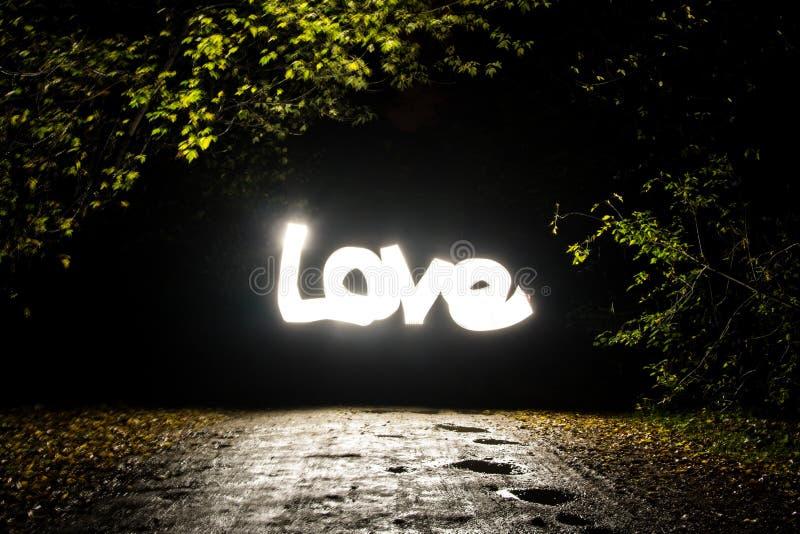 Amour rougeoyant de mot dans le Freezelight foncé photo stock